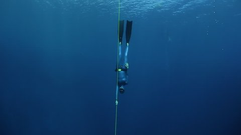 Woman freediver descends along the rope in a sea. Blue Hole, Dahab, Egypt.