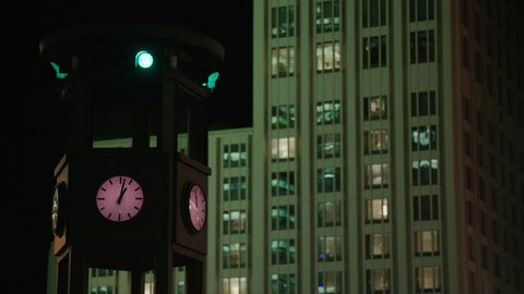 May, 2017 Berlin, Germany. Clock and street light at the Potsdamer Platz at night, traffic light changes color with pan right to left.