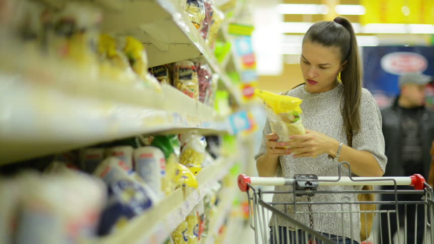 Attractive Young Woman with Long Dark Hair and Sensual Lips Choosing Spaghetti Standing Near Shelf With Goods in the Hypermarket. | Shutterstock HD Video #32357314