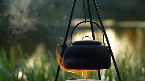 Boiling kettle on the fire outdoor slow motion