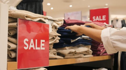 Female Hands Choosing Jeans from Stack in Clothing Store. Big Red Sale Sign in Shopping Mall. Black Friday Concept. 4K.