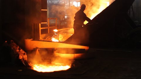 Hard work in the foundry, workers controlling iron smelting in furnaces, too hot and smoky working environment
