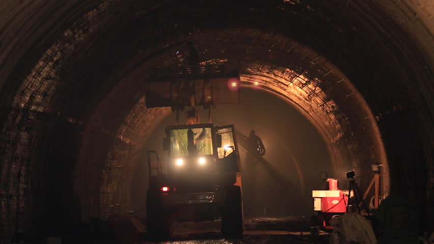 Preparatory works for construction of tunnel. Repair of way that passes through the mountains. People work under the ground in tube. Transportation engineering. Workers operates machines in dark