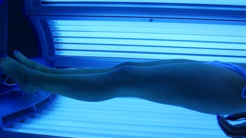The girl is in the solarium. Young sexy woman in a bikini sunbathing.