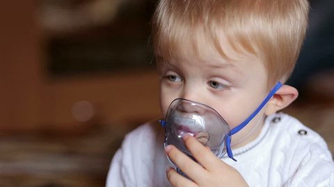 Nebulizer for inhalation, sick child breathes through nebulizer, baby does inhalation, boy with an oxygen mask on his face, treatment at home, medical procedure.