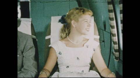 1950s: Woman reclines seat on airplane, lays back, closes eyes, smiles. Brooklyn bridge, Rockefeller Center, United Nations building.