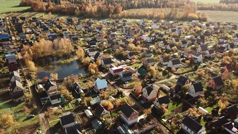AERIAL SHOT: Beautiful small village or township in the autumn forest. A lot of houses roofs around. Drone is turning right.