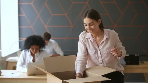 First day at new job concept, young happy woman unpacking box with her belongings standing near office desk, just hired smiling intern starting work in big company, moving into coworking space