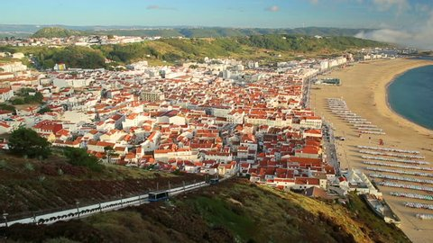 Time lapse of picturesque Nazare in Portugal by sunset light, most popular seaside resorts in Atlantic coast. Trains of Nazare Railway Funicular. Nazare Skyline and beach waterfront from Nazare Sitio.
