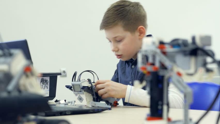 Smart school boy assembling robot. 4K. | Shutterstock HD Video #32434444