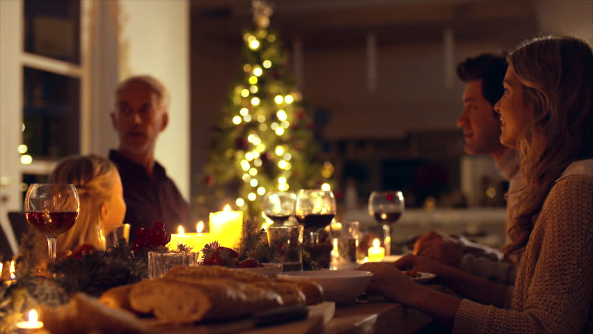 Happy family celebrating christmas together at home. Family sitting at dining table talking and having dinner together on Christmas eve.   Shutterstock HD Video #32437927
