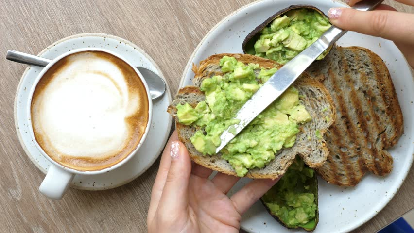 Top View Of Healthy Breakfast With Avocado Toast And Coffee In Cafe. Closeup. 4K.
