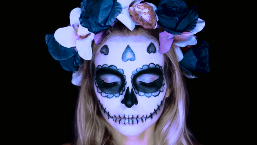 Closeup face of woman with Mexican sugar skull makeup and flowery wreath opening eyes and looking into the camera. Creative, artistic, Halloween concept - slow motion video