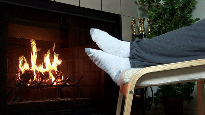 A man sitting next to his living room fireplace warming his feet by the cozy fire.