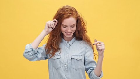 Happy ginger woman in denim shirt dancing and looking at the camera over yellow background
