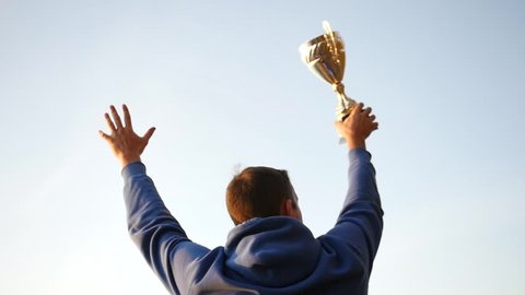 The winner with a reward in his hands raises his hands up, rejoices at the success. slow motion, 1920x1080, full hd