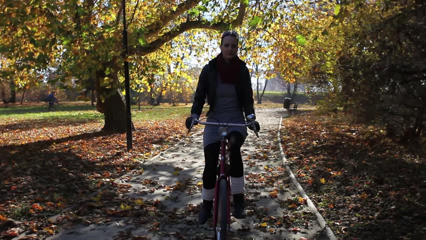 Young woman riding on bike in autumn setting. Edited Sequence.