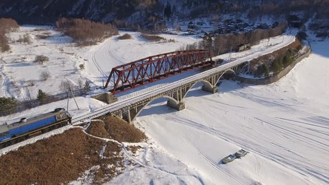 Passengers train Trans Siberian railway metal bridge. Frozen lake Baikal coast. Winter beautiful tourism Russia. Sunny day snow field high rocks. Fast speed aerial drone 4k footage.