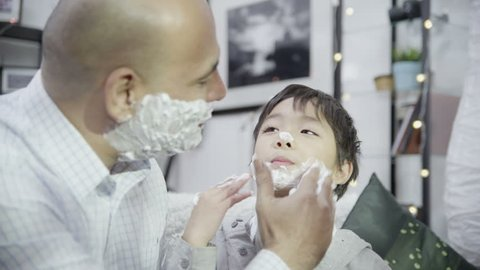 Loving father teaches his cute young son how to apply shaving foam to his face. In slow motion.