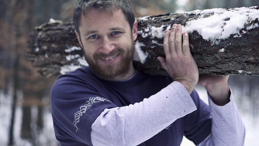 Portrait of happy lumberjack with log, super slow motion, shot at 240fps