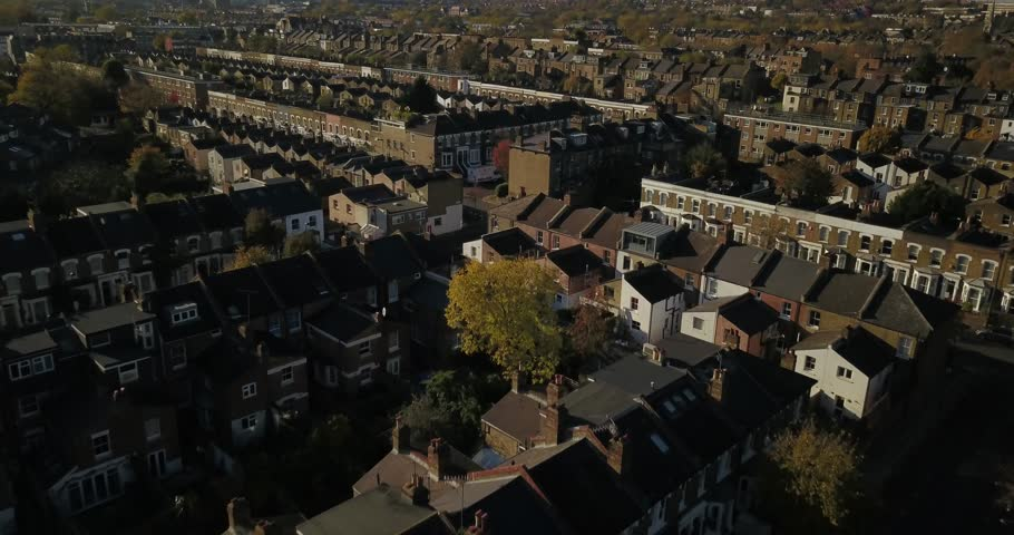 Aerial drone footage, sweeping shot of residential buildings in North London, UK.