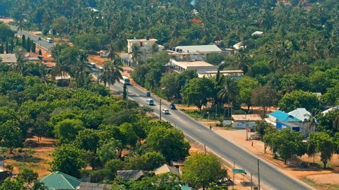 Cinematic aerial of busy traffic on streets of city of Dar es Salaam by Indian ocean in Tanzania, Africa. Cars, busses, motorcycles, pedestrians, lush, green vegetation, palm trees, hot summer day