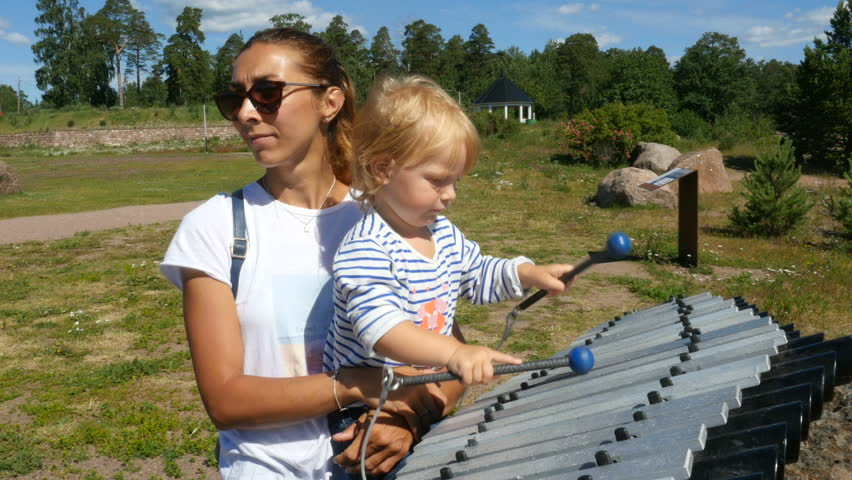 Small kid plays the xylophone. Kid walking with mom in park