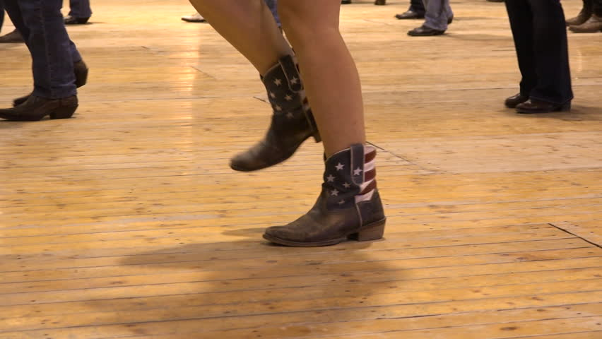 Woman dancing cowboy line dance at a folk country event, USA style. Female feet cowgirl stepping at American horse festival. Music tradition jeans boots and flag