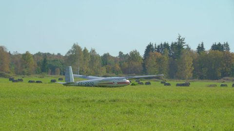 A white commercial sailplane landing on the grass with the car on the side waiting