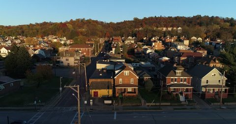 A profile moving aerial establishing shot of a typical Pennsylvania small town at sunset. Pittsburgh suburbs.