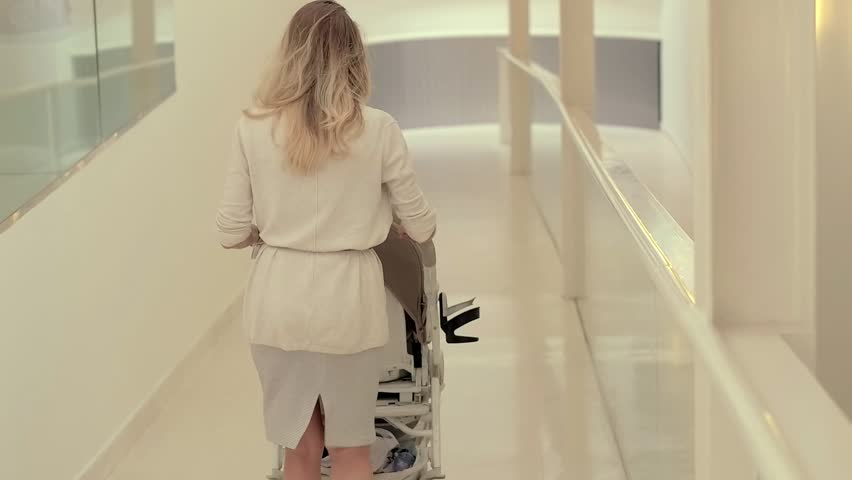 Young mother with children in baby stroller walking on corridor back view. Mom with child in baby carriage going out in corridor for walk | Shutterstock HD Video #32668498