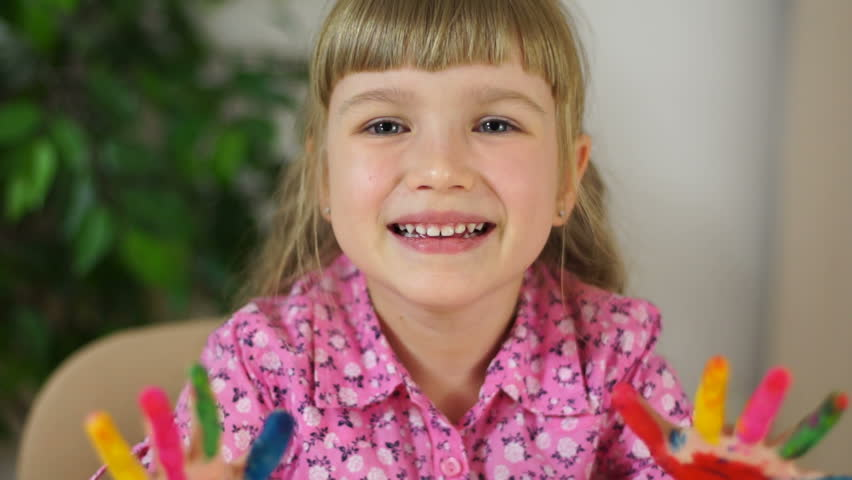 Closeup portrait funny girl coloring. Girl covered in finger paint. Selective