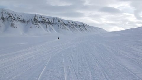 Snowmobile snow bike in North Pole Spitsbergen Svalbard Arctic. Way from airport Longyear to Pyramiden on background of glacier.