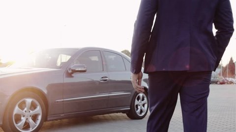 Man in a suit Walks tTowards The Luxury Car, unlocks it, sits in. Successful Lifestyle, Stylish Look. Lifestyle Motivation, Rich Person. Power, Money, Glory.