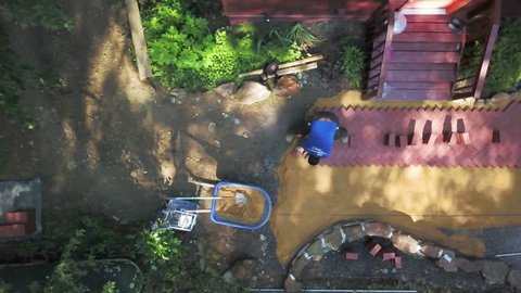 Aerial camera looking straight down showing a hardscape worker putting brick pavers into a herringbone pattern on a backyard patio