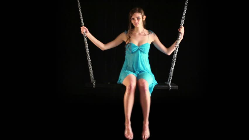 Attractive girl in blue dress sways at swing which hang on chains under rain