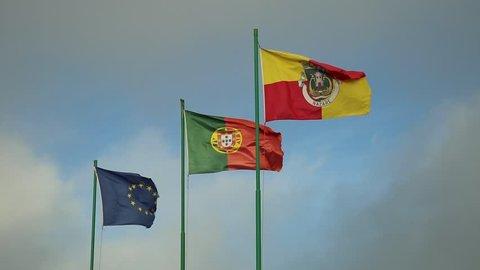 Flags of European Union, Portuguese flag and Nazare Flag waving in the blue sky. Miradouro do Suberco in Nazare Sitio, Central Portugal, Atlantic coast.