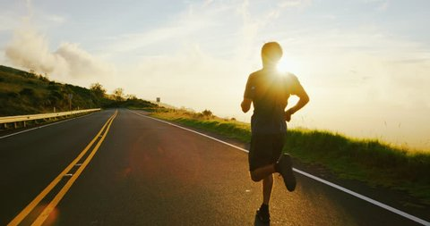 Athletic young man running on the road at sunset in slow motion
