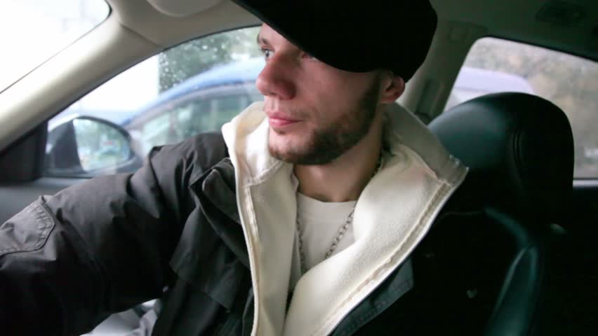 Adult rapper rapping in car on street, shown in motion