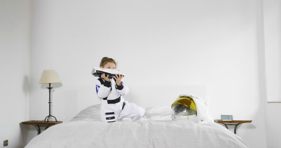 Portrait of a little girl dressed up by astronaut playing with shuttle and smiling while watching the camera. Concept of: ambition, success, children and their future. | Shutterstock HD Video #32782018