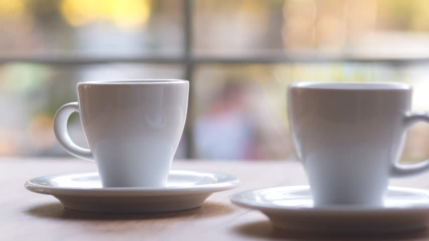 SLOW MOTION: Two cups of espresso coffee on a wooden table indoors. Morning coffee, morning ritual. Coffee for two at home by the window. | Shutterstock HD Video #32784034