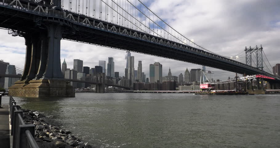 A tugboat pushes a barge down the East River, past the Manhattan Bridge, in New York City. | Shutterstock HD Video #32789443