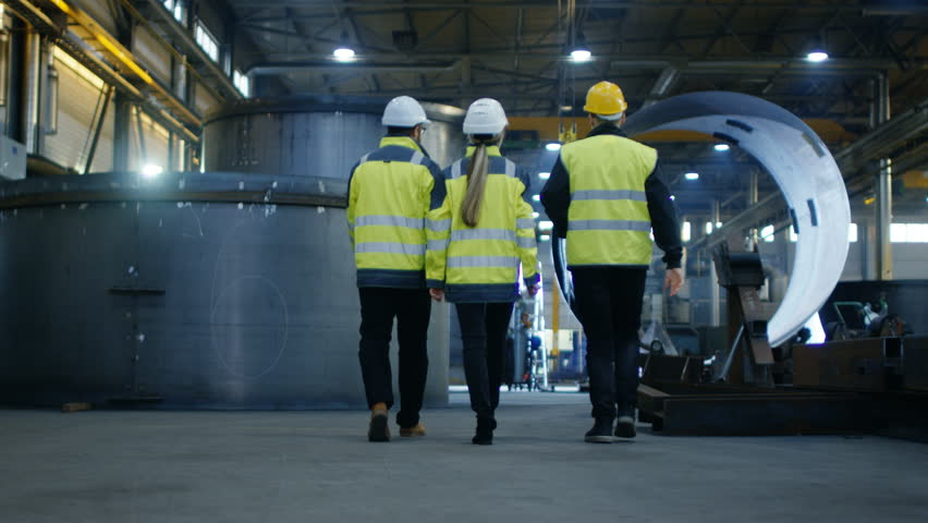 Following Shot of Three Engineers Walking Through Heavy Industry Manufacturing Factory. In the Background Welding Work in Progress, Various Metalwork, Pipeline/ Barrel Components. Slow Motion. #32793214