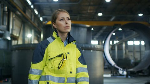Female Industrial Worker Puts on Protective Hard Hat while Walking Through Heavy Industry Manufacturing Factory. In the Background Various Metalwork Components are Seen. Shot on RED EPIC-W 8K Camera.