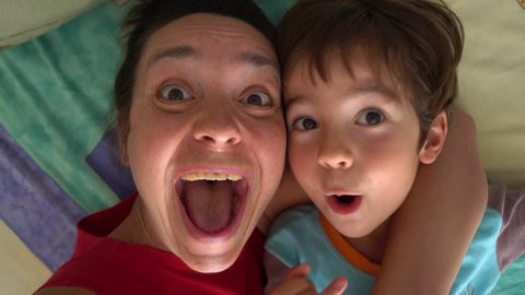 4K Crazy mother and son play monkey on selfie camera