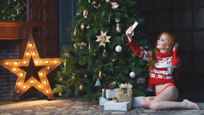 Seductive redhead girl in red lingerie sitting near Christmas gifts and makes a selfie. Christmas holiday season. | Shutterstock HD Video #32838844