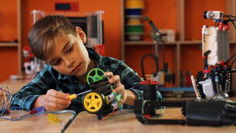 Portrait shot of nice blonde boy with the screwdriver assembling a robot and smiling straight into the camera in the modern comfortable playing space of classroom.