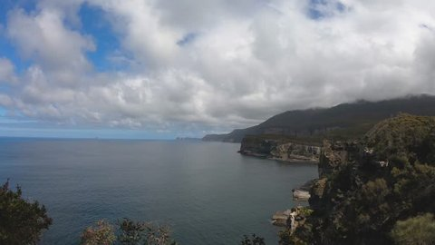 View of mountains, ocean and coast, from the Tasman Arch Lookout, on a bright sunny day, Tasmania, Australia