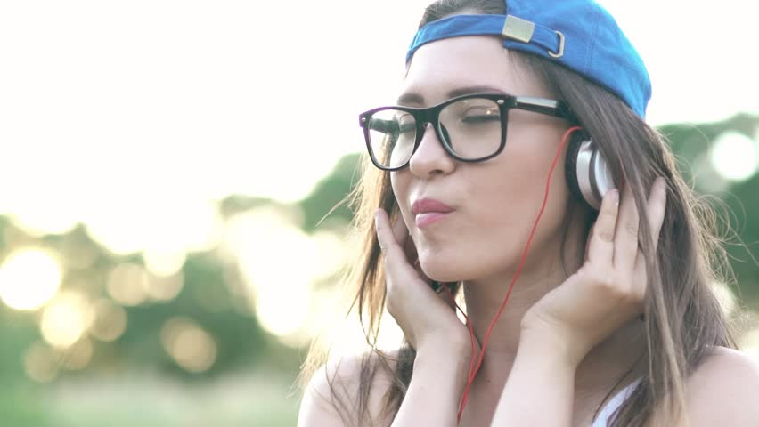 SLOW MOTION:Portrait of hipster girl with headphones blowing bubble gum   Shutterstock HD Video #32891017