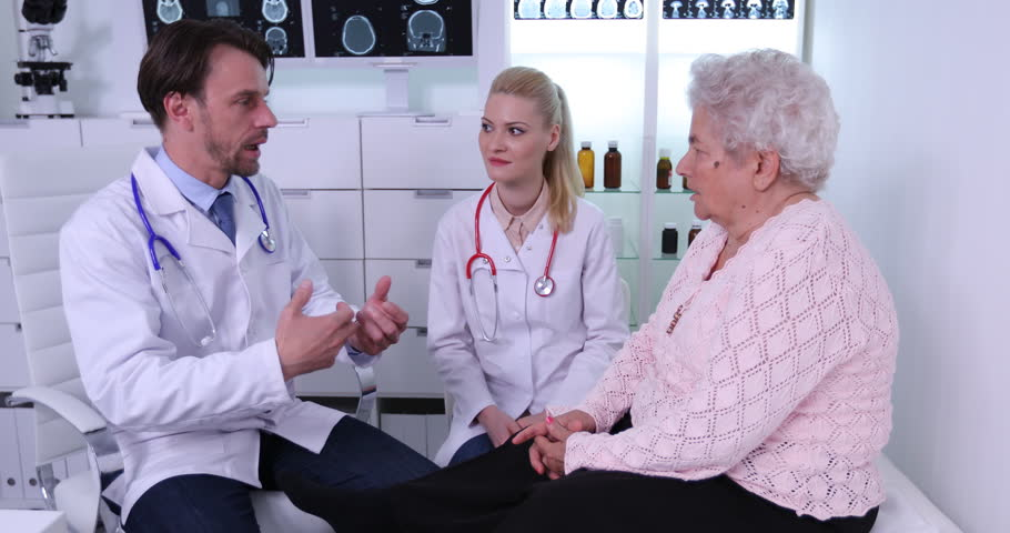 Doctor Man and Woman Talking About Therapy Procedure in Cabinet with Old Patient | Shutterstock HD Video #32903944
